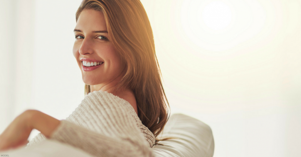 Smiling young woman wearing beige sweater looking over her shoulder at you