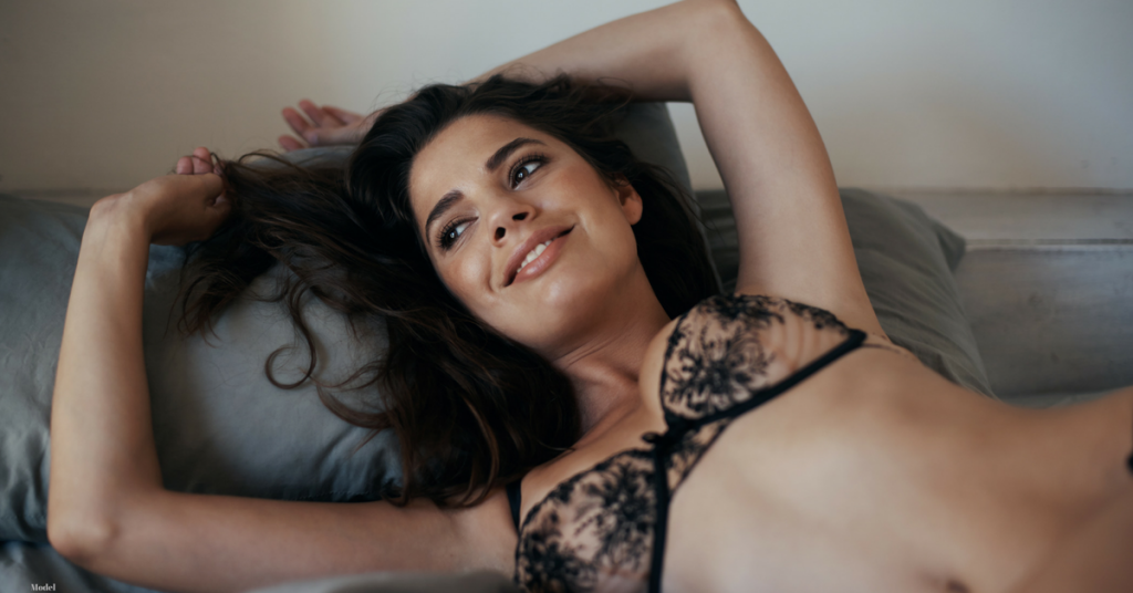 Young woman with dark hair laying on her back with arms over her head wearing a lacey black bra