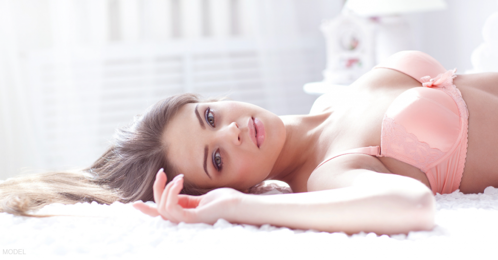 Portrait of a woman laying down after a breast augmentation by a board certified plastic surgeon in Sacramento, CA