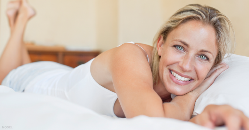 A woman smiles after a successful breast augmentation procedure in Sacramento, CA
