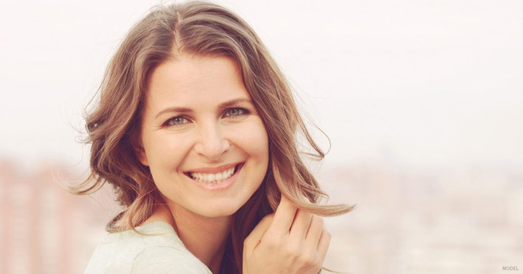 Face of smiling woman with light brown hair and her right hand near her cheek