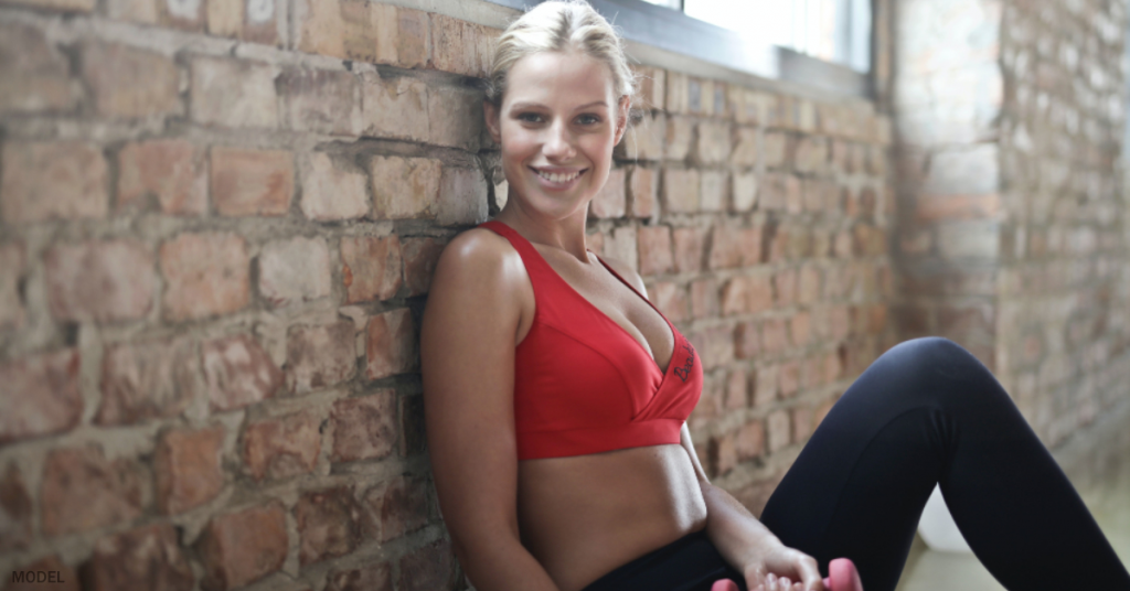 Smiling, young, blonde woman in workout clothes sitting against a brick wall with a small, pink dumbell in her hand