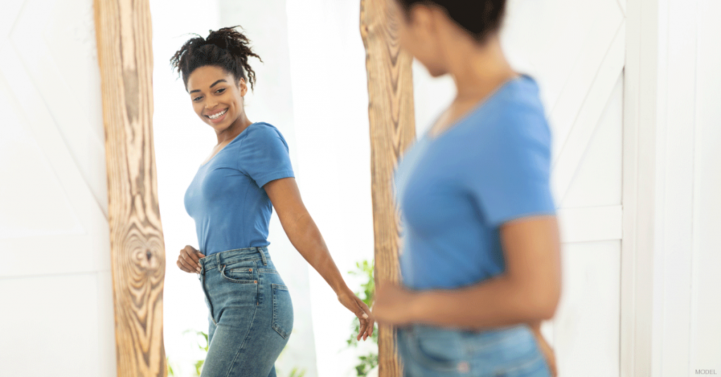 Woman in Sacramento, CA admiring her results after liposuction